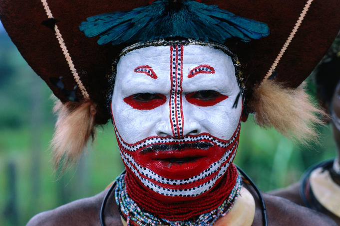 Man in traditional headdress and face paint.