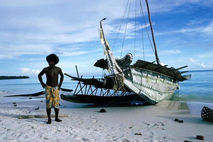 Man stands next to traditional trading canoe, Trobriand Islands.