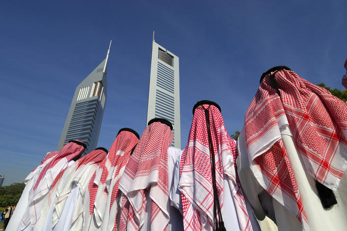 Traditional dancers with Emirates Towers in background.