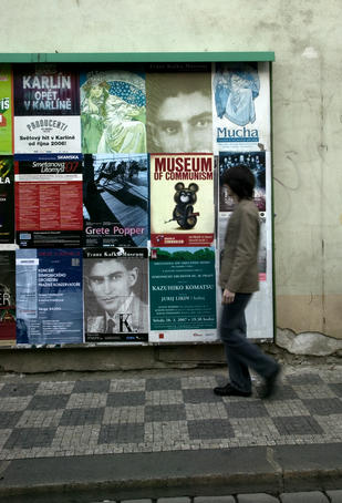 Local man passing billboard with Kafka posters.