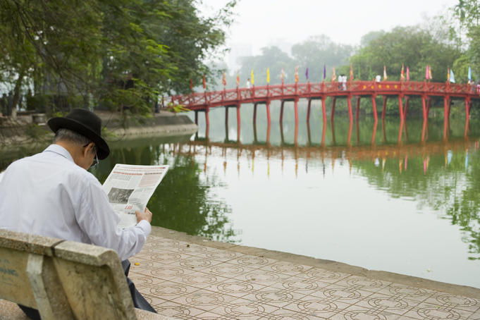 Man reading paper beside The Huc Bridge on Hoan Kiem Lake.