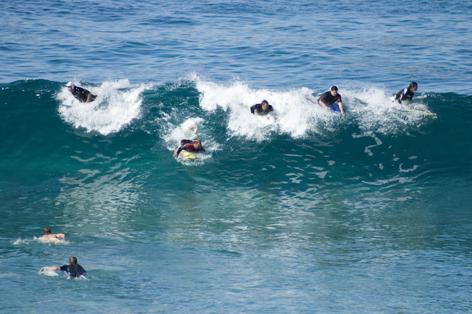 Surfers catching wave at Bronte Beach.