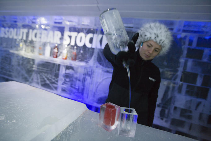 Woman serving vodka drinks in ice glasses at Absolut Icebar, Nordic Sea Hotel.