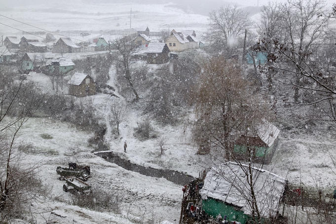 Winter snows begin to fall on village, Transylvania.