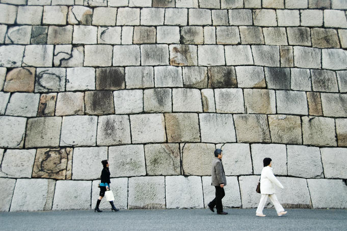 People walking past the massive stone wall of Tenshudai Donjon in Higashi-gyoen (Imperial Palace East Garden).