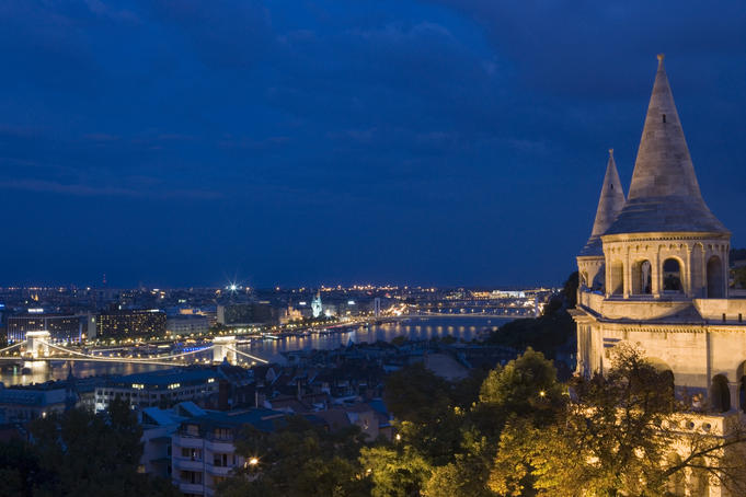 Fisherman's Bastion at night with city lights below.