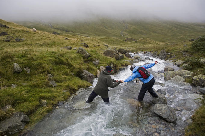 Walkers crossing stream on Loft Beck, Lake District.