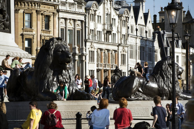 Bronze Lions at Trafalagar Square with Whitehall architecture in background.