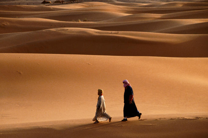Men walking across sand dunes.