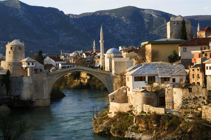 Reconstructed Old Bridge spanning the Neretva River with reconstructed buildings and mosques of the Ottoman/Turkish quarter in background.