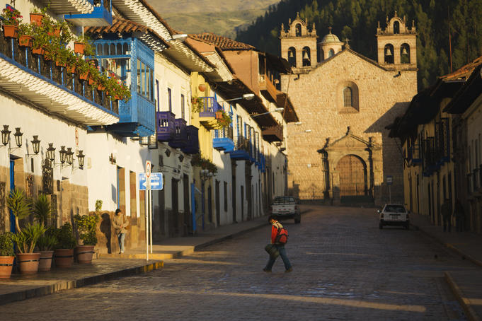 Person walks through quiet morning streets in Cusco.