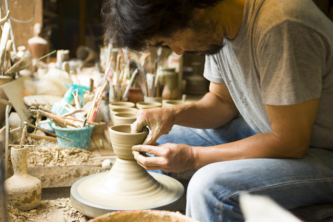 Potter making pottery bowls on a potter's wheel at Kageyama Pottery.