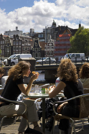 Patrons sit along Kloveniersburgwal canal at Cafe De Jaren in central Amsterdam.