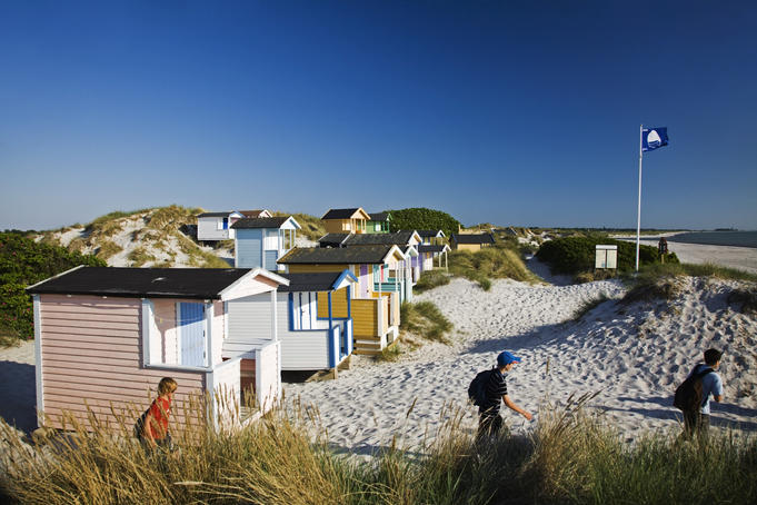 Small beach huts in dunes by the beach.