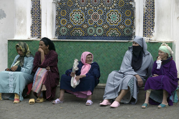 Women sit on the side of the street, Moulay Idriss