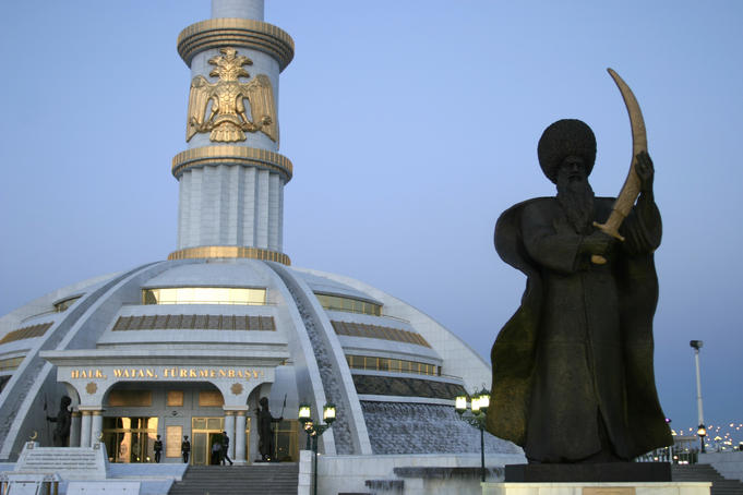 Statue in front of monument to Independece of Turkmenistan.
