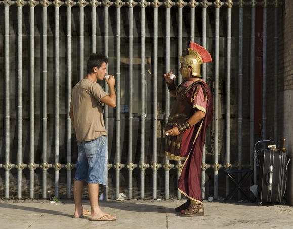 Man in gladiator costume at Colosseum taking a drink break.