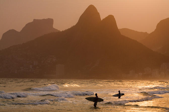 Surfers at sunset on Ipanema Beach, with the twin peaks of Morro Dois Irmaos (Two brothers mountain) in backgound.
