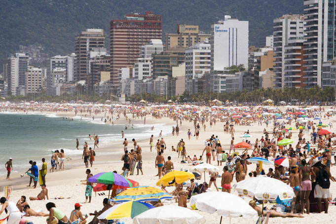 People enjoying the beach and surf at Ipanema Beach.
