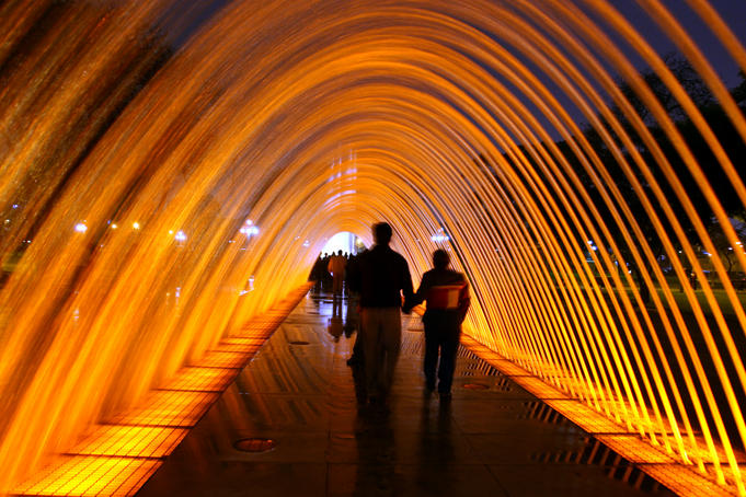 People walking through one of the 13 illuminated fountains at Lima's Parque de la Reserva