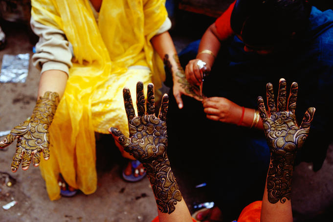 Henna artist working on a customer's hands in Main Bazaar, Parharganj.