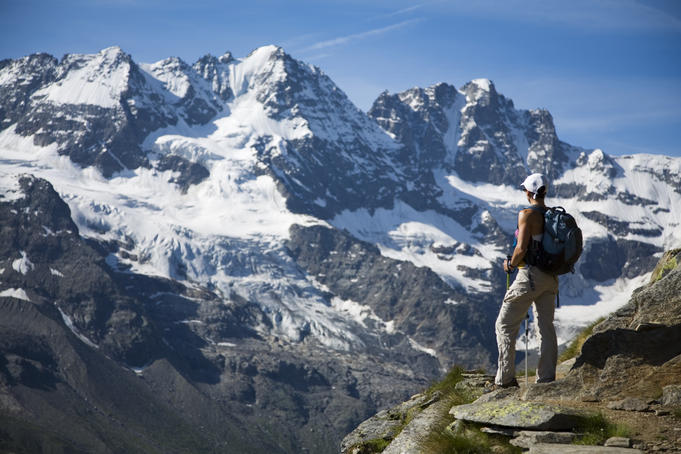 Hiker on traverse from Refugio Vitorio Sella to Herbetet with mountains of Gran Paradiso massif in background.