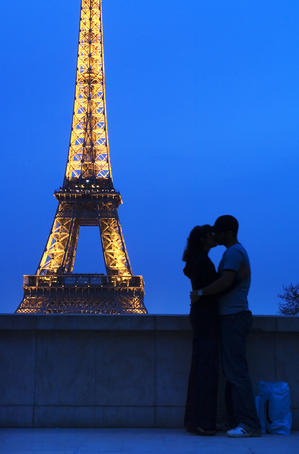 Lovers kissing in front of the Eiffel Tower at night.