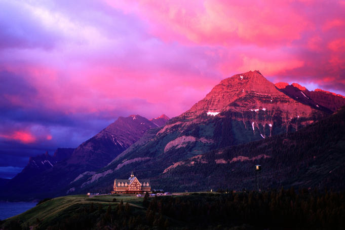 Prince of Wales Hotel and Canadian Rockies under a brilliant pink and orange-hued cloudy sky.
