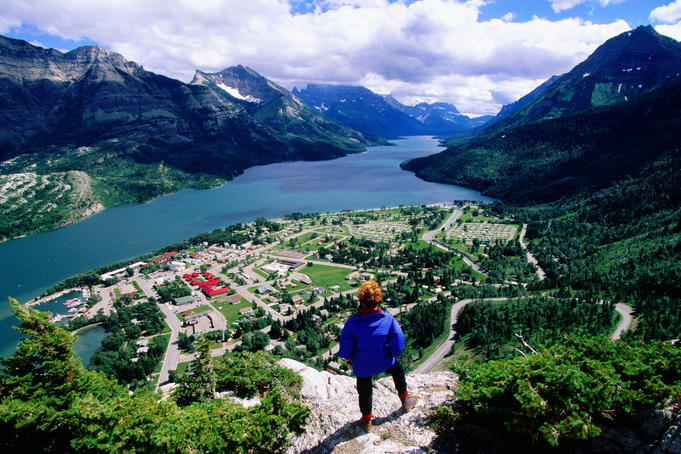 Hiker overlooking Waterton town, Waterton Lake and Canadian Rockies from Bear Hump.