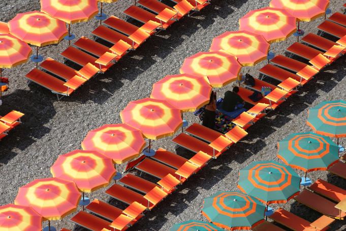 Beach umbrellas and chairs lining black sand beach, Amalfi Coast.