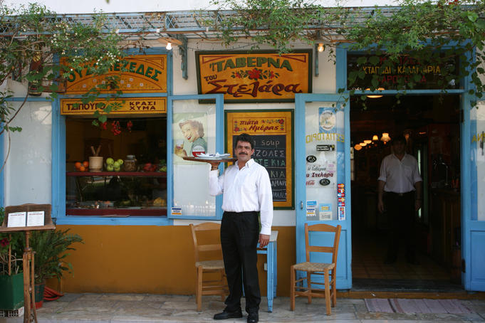 Waiter standing in front of tavern.