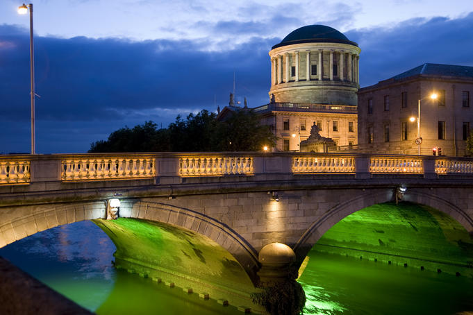 Illuminated Four Courts building and bridge over the River Liffey.
