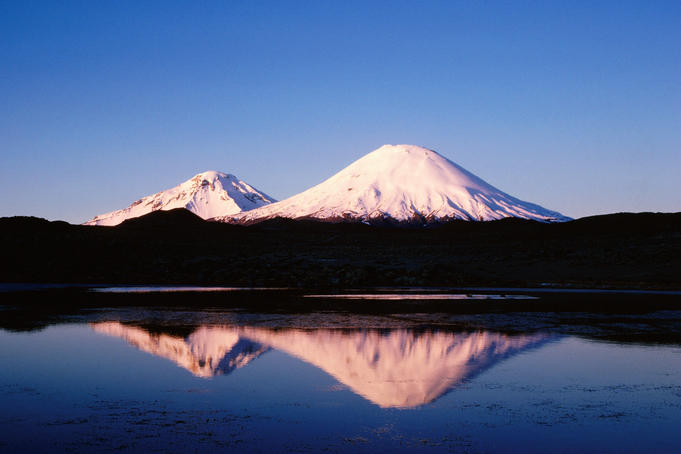 Parinacota and Pomerape volcanoes at sunset, with reflection in high-altitude lake, Norte Grande region.