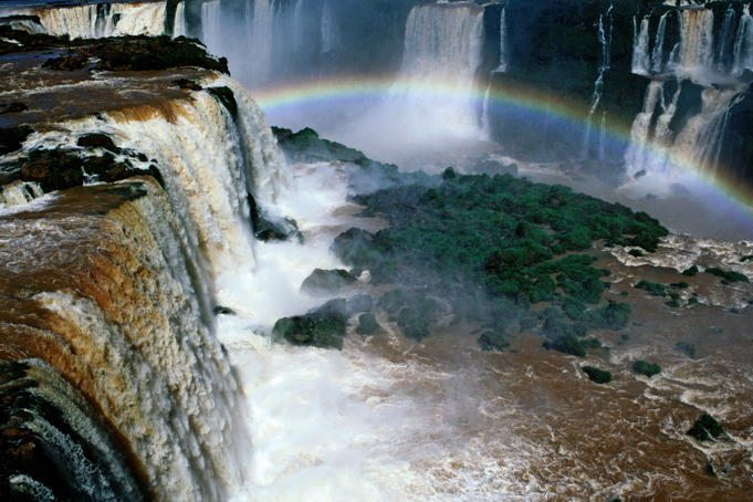Rainbow spanning part of Iguazu Falls, seen from Brazilian shore.