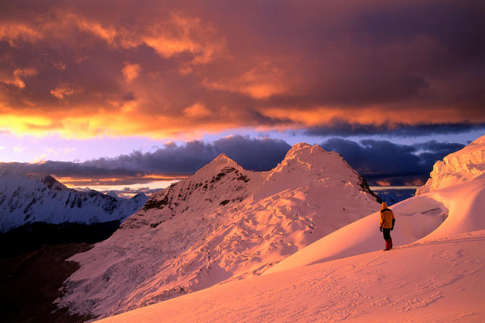 Climber on orange-tinted glacier above Ishinca Valley at sunset, Cordillera Blanca range.