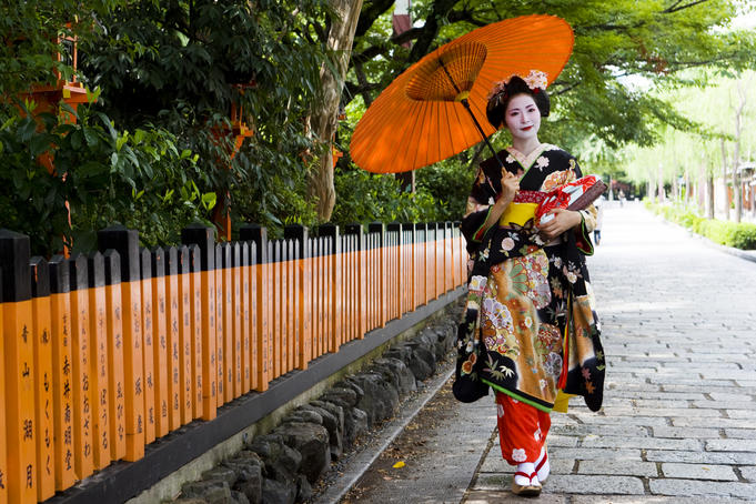 Young maiko (apprentice geisha) girl, walking with umbrella, in Shirakawa-miname-dori street.