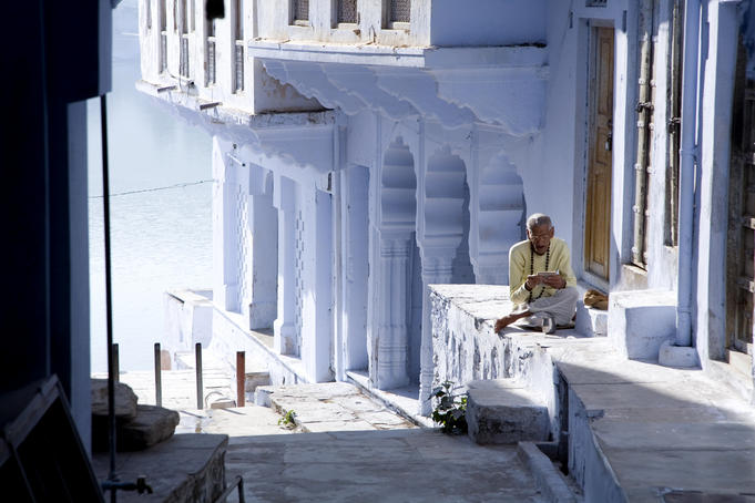 Man reading near the ghats of Pushkar Lake.