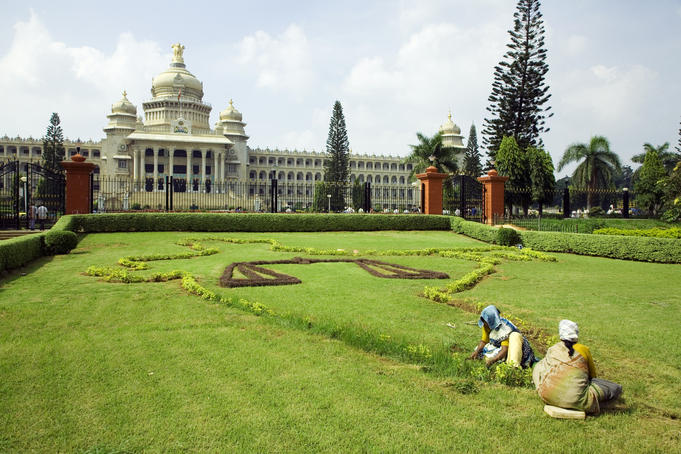 Workers on lawn outside the Vidhana Soudha, which houses the state legislature.