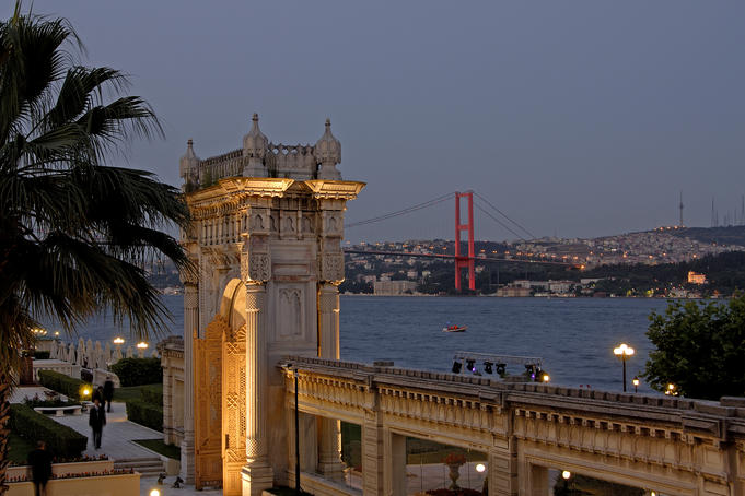 Palace Gate of the Ciragan Palace, with the Bosphorus Bridge spanning the Bosphorus Strait.