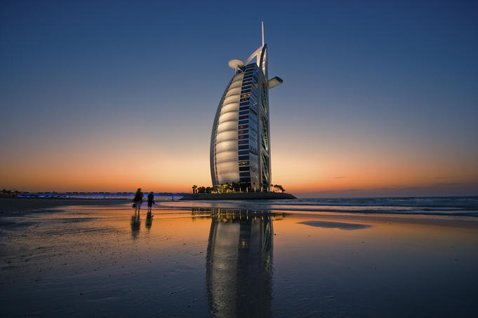 Burj Al Arab Hotel reflected on beach at sunset.