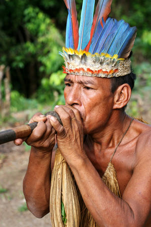 Yahua tribesman demonstrates shooting poison darts from a blowpipe at his village on the Nanay River.