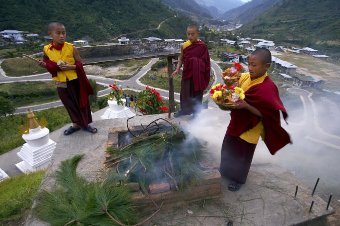 Young, future Buddhist monks making smoke offerings of juniper.