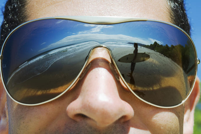 Reflections in shades of a surfer looking at the waves.