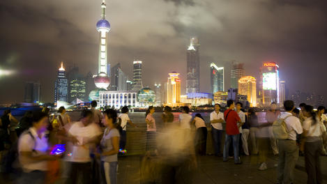 People socialising on the Bund promenade at night, with Pudong skyline in background.