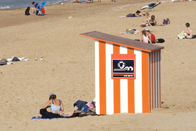 Wooden beach hut and sunbathers.