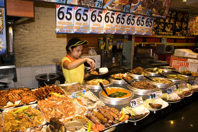 Woman serving food at food court restaurant, Robinsons Place.