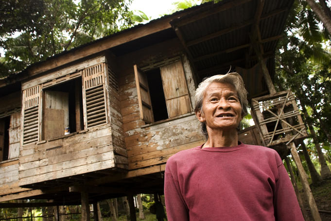 Man outside his rural wooden house.