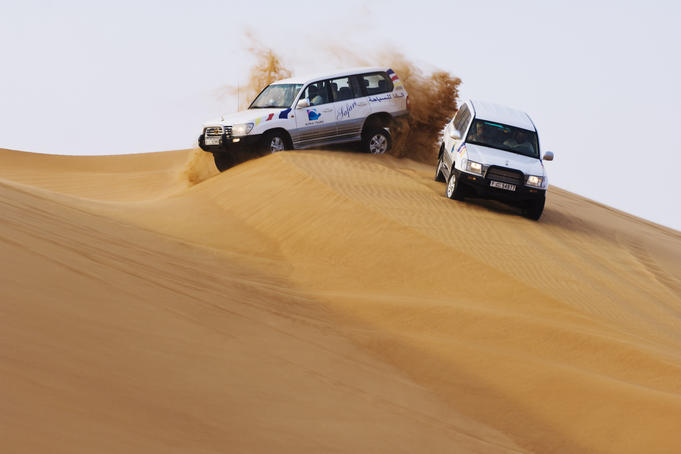 Jeeps negotiating sand dunes on jeep safari in Arabian Desert.