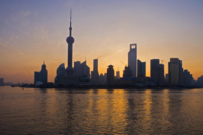 Pudong skyline & Huangpu River at sunrise from River Promonade on the Bund.