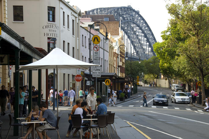 Outdoor dining at The Rocks Cafe, 99 George Street, The Rocks, with Sydney Harbour Bridge in background.